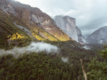 Tunnel view at Yosemite valley - Green trees on mountain under cloudy sky during daytime. San Diego. A view of a snow covered mountai