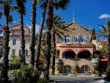 promenade - in a seaside resort. A large stone building with palm trees.