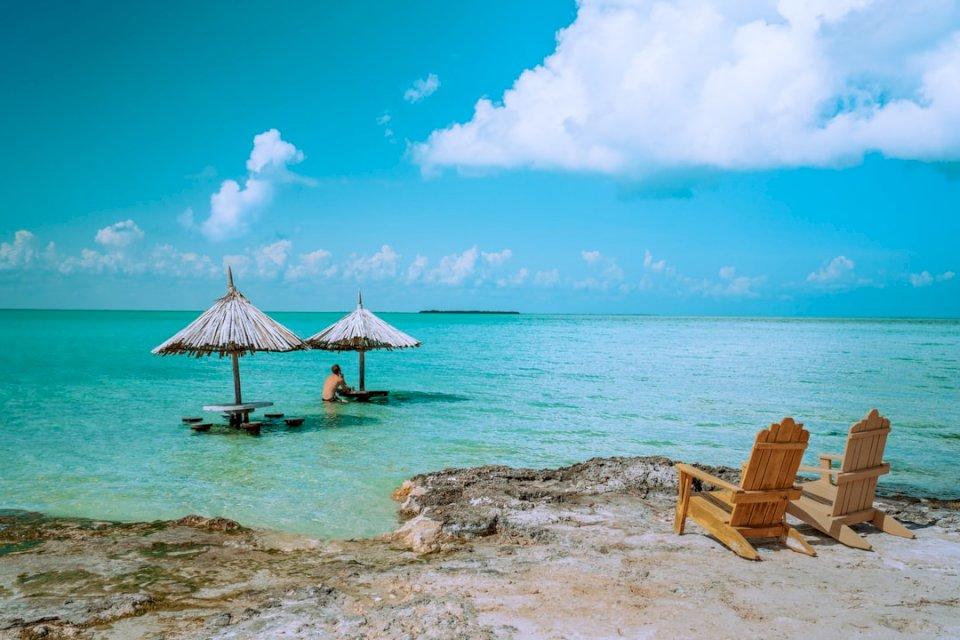 Mężczyzna siedzący samotnie w raju. - Brown drewniani holów krzesła na plaży podczas dnia. Kalifornia. Grupa leżaków na piaszczystej
