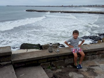 ayrton on the beach - Mar del Plata vacation with mom. A person sitting on a bench near the water.