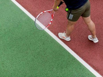 Male sports engineer tests - Person in black shorts holding red and white tennis racket.