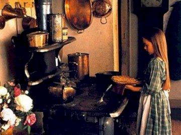 tjej cookin - liten flicka som lagar mat på gammal vedspis