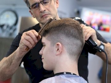 hairdressing services - the barber cuts the boy's hair