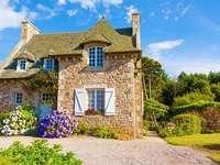 Малка къща, заобиколена от цветя