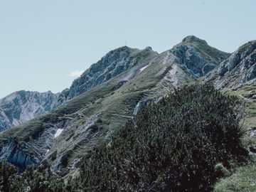 1970er 35mm Film Diafoto eines Berghangs - grüne Wiese nahe Berg unter blauem Himmel während des Tages.