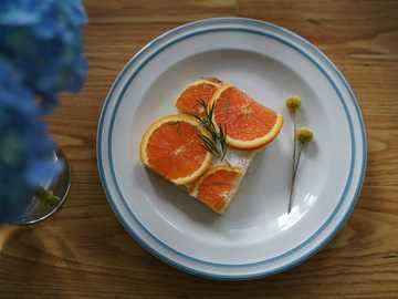 brunch  cake toast - sliced orange on white ceramic plate.