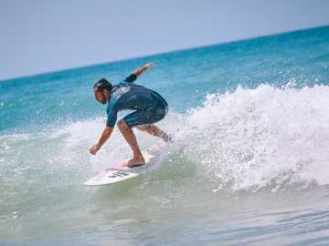 Surfing Andalucia - person riding a surfboard on a body of water. El Palmar, Spain