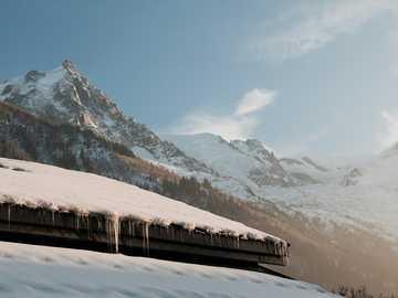 Mont Blanc i dach domu ze śniegiem. - ośnieżony dach i góry pod niebieskim niebem. Chamonix, Francja