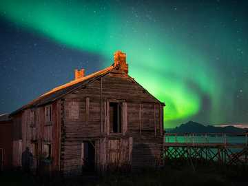Spectacular Night Skies - brown wooden house near body of water. Hovden, Norway