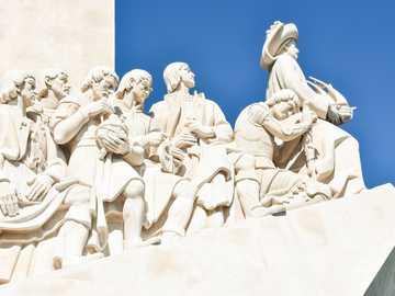 Los grandes exploradores - estatua de hormigón blanco bajo un cielo azul durante el día. Lisboa, Portugal