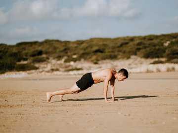 Mann trainiert - Mann macht Push-up auf Sand.
