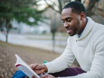 Lire à Atlanta - homme portant un chandail blanc lors de la lecture du livre. Atlanta, États-Unis