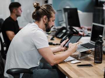 Jack pracuje w biurze Studio Republic w Winchester - mężczyzna trzyma włączonego iPada przed wyłączonym MacBookiem Air. Studio Republic, Winchester