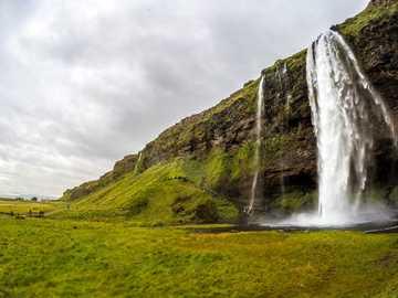 cascada bajo cielo nublado - Disfruta de los increíbles paisajes islandeses. Estamos viajando por el camino para admirar la magn