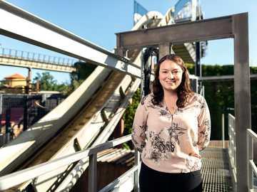 Inżynier budownictwa z kolejką górską - kobieta w biało-czarnej kwiecistej koszuli z długim rękawem stojącej na moście w ciągu dnia.