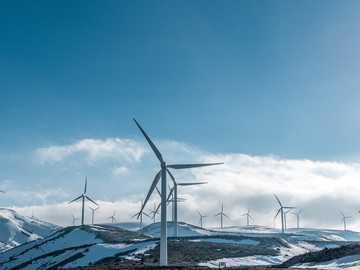Windturbinen auf schneebedeckten Bergen unter klarem blauem Himmel während des Tages - Alle Windkraftanlagen produzieren nebeneinander reinen Strom, ohne unseren geliebten Planeten Erde z