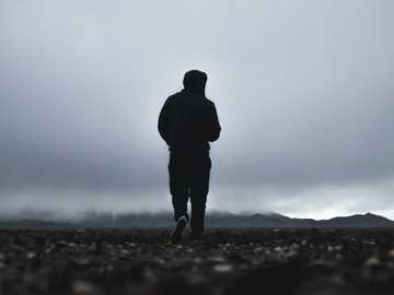Misty Solitude - silhouette of person walking in front of mountain.
