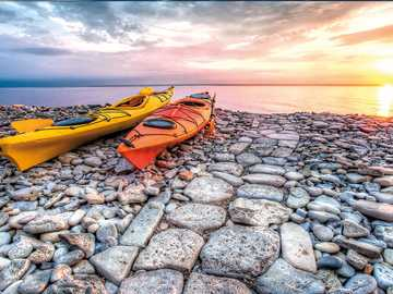 Kayaks on the rocky beach - Sunset over the ocean
