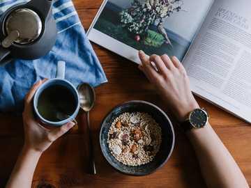Desayuno relajante - Persona con taza de cerámica azul y revista blanca. Melbourne, Australia