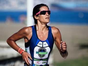 fotografia selektywnej ostrości kobiety z systemem - Triatleta durante la carrera a pie por el Paseo Marítimo Antonio Banderas de un triatlón celebrado