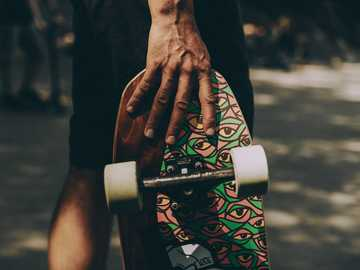 Skateboard - person holding brown wooden round table.