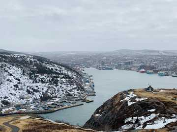 Nature blends in with urban - people on beach during daytime. Signal Hill National Historic Site, St. John's, Canada