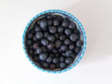 A bowl of washed blueberries. - black round fruits in blue ceramic bowl. Manchester, UK