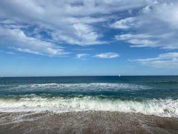 Morze Śródziemne vía Barcelona - osoba stojąca na brzegu plaży pod błękitne niebo i białe chmury w ciągu dnia. Plaża Barcelone