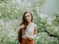 Coy Yet Confident - selective focus photography of woman in tank top standing in forest.