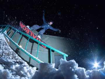 man riding on snowboard at nighttime - Urban street snowboarding - jibbing the rail.