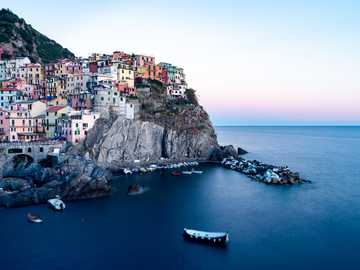 The village of Manarola in Cinque Terre, Italy. - city buildings on cliff by the sea during daytime. Manarola, SP, Italy