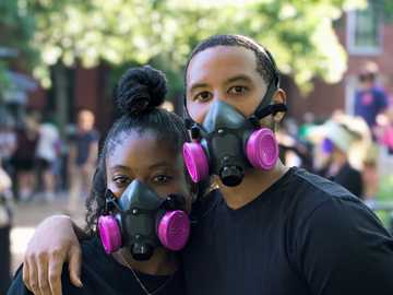 man in black crew neck t-shirt wearing purple and green gas mask - A Couple wearing pink accented gas masks joins the Protests in Washington DC.