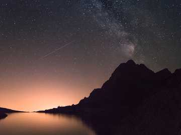 Starry sky over the Tatras - silhouette of mountain beside the body of water at night time. Téryho chata, Vysoké Tatry, Slovaki