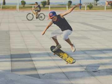 Kid skateboarding on the Batumi Bay - man in blue t-shirt and white shorts riding on skateboard during daytime. Batumi Bay, Batumi, Georgi