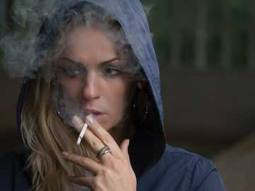Woman in hoodie smoking - woman wearing hoodie while holding cigarette. Люберцы, Lyubertsy, Russia