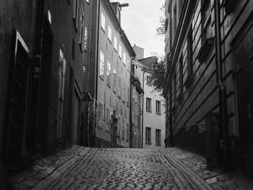 Deserted old streets - grayscale photo of empty street between buildings. Stockholm, Sweden