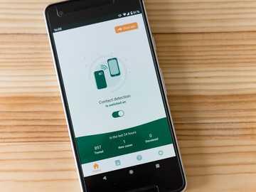 Application de détection des contacts Corona - smartphone android samsung noir sur une table en bois marron.