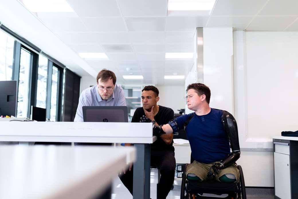 Gli ingegneri guardano lo schermo del computer con l'utente dell'arto protesico