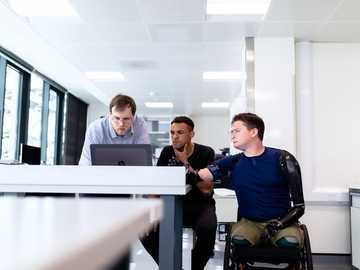 Engineers look at computer screen with prosthetic limb user - man in blue dress shirt sitting on black office rolling chair.