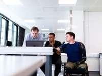 Οι μηχανικοί βλέπουν την οθόνη του υπολογιστή με προσθετικό άκρο χρήστη - άντρας σε μπλε φόρεμα πουκάμισο που κάθεται στο μαύρο �