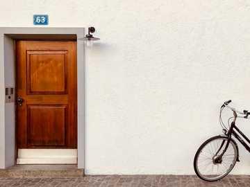 Minimalist times in Switzerland. - black bicycle leaning on white wall. Altstadt Kleinbasel, Basel, Switzerland