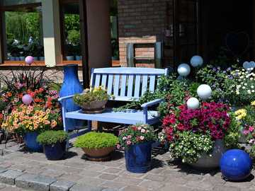 A place to relax - patio with a bench among flowers