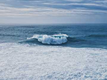 Vague massive à Nazaré - vagues de la mer blanche sur le sable blanc pendant la journée. Nazaré, Portugal