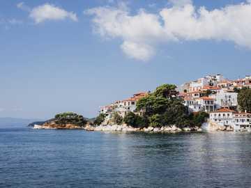 Skiathos, Grecia. - edificios en la isla frente a la masa de agua bajo el cielo azul. Skiathos, Grecia