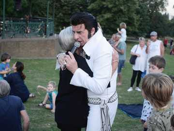 woman hugging man holding microphone - A summer evening in Hampsted Heath with a Elvis impersonator. Hampstead Heath, London, United Kingdo