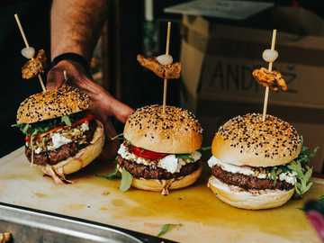Podawane są burgery. - osoba trzymająca burger z pasztecikiem i serem.