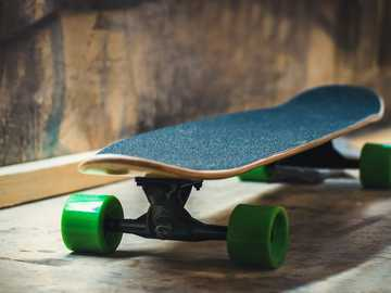 longboard - black skateboard on brown surface.