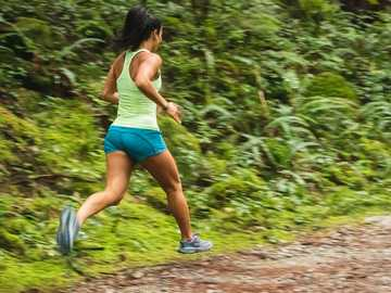 female runner on trail in the forest - woman in white tank top running on dirt road during daytime.