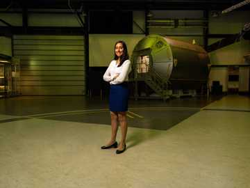 Female space operations engineer in hangar - woman in white shirt and blue denim shorts standing on green floor.
