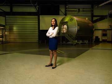 Inżynier operacji kosmicznych w hangarze - kobieta w białej koszuli i niebieskich jeansowych szortach stojących na zielonej podłodze.